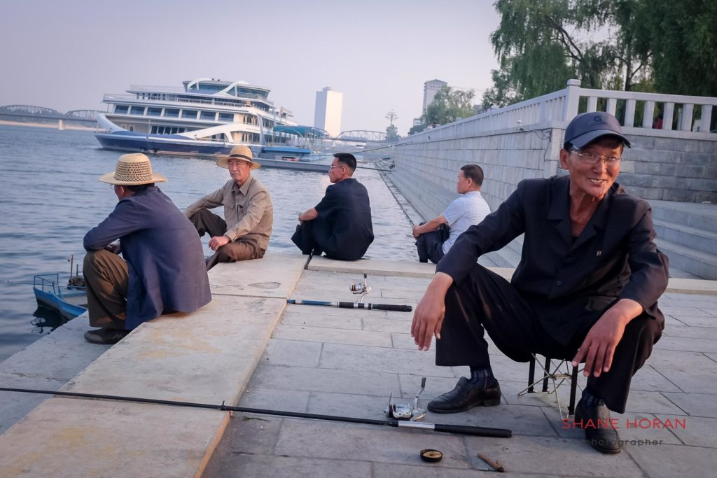 Just off Kim Il Sung Square, men recall tales of fighting fish caught from the Taedong river, Pyongyang, North Korea