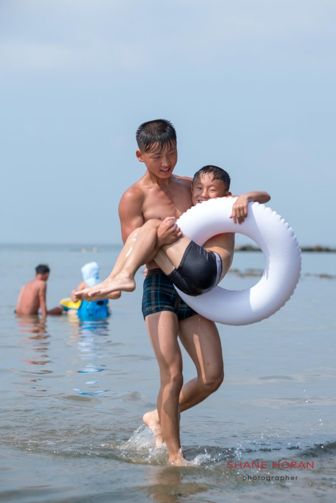 Brothers emerge from the water at Nampo Beach, North Korea