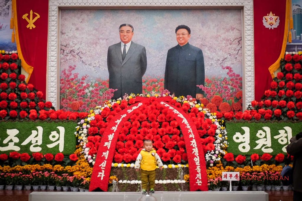 Toddler posing for a photograph with Kim Il Sung and Kim Jong Il at the Kimjongilia flower exhibition, Pyongyang, North Korea