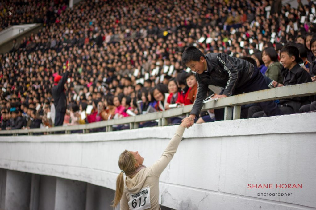 Foreigner reaches out to shake the hand of a local during the Pyongyang marathon opening ceremony, 2015. Kim Il Sung stadium, Pyongyang, North Korea