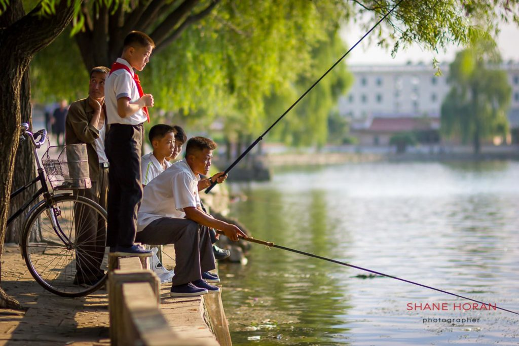 Men and boys fish under the glow of the evening light in Sariwon, North Korea