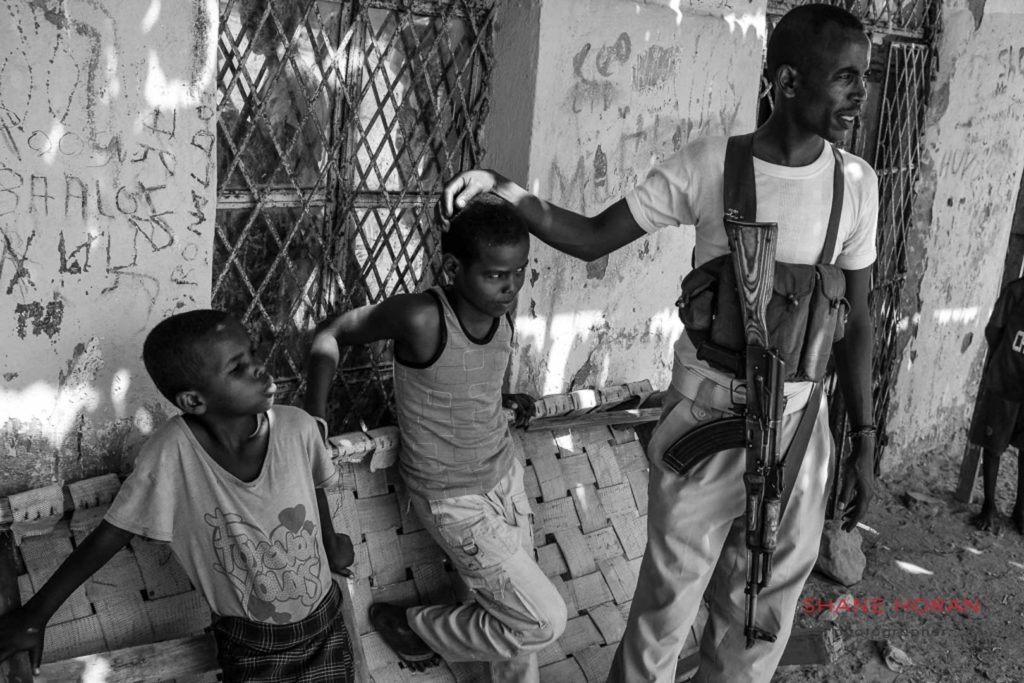 Guard hangong out with local boys in Berbera, Somaliland
