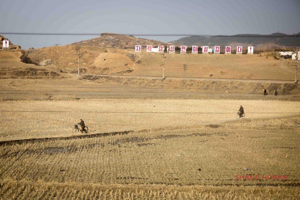 North Korean villagers make their way through a field