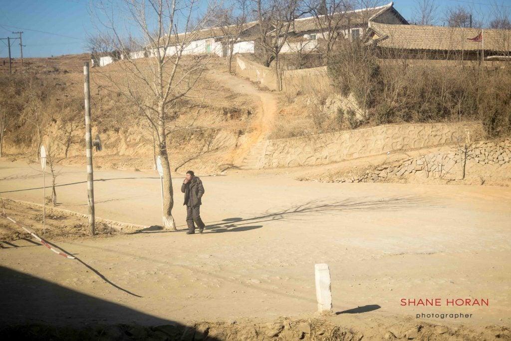 North Korea man smokes while watching the train pass