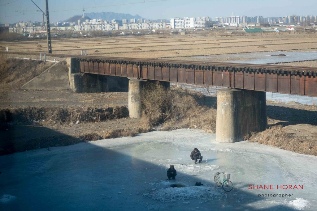 Ice fishing near Sinuiju, North Korea. Dandong China is visible in the background