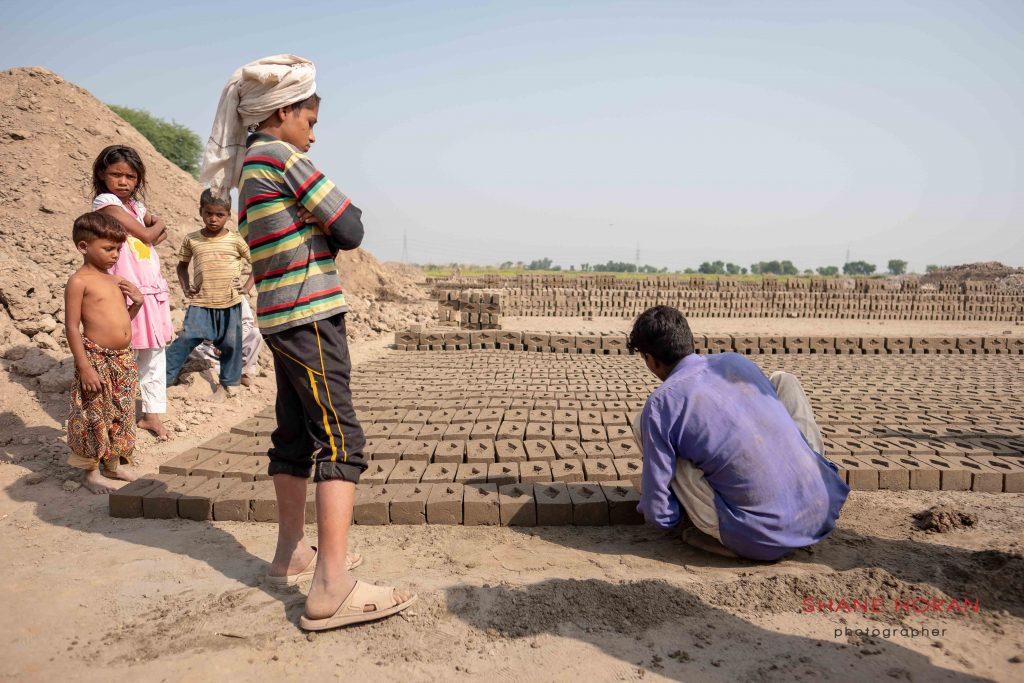 Family  members watch the brick making process, Pakistan